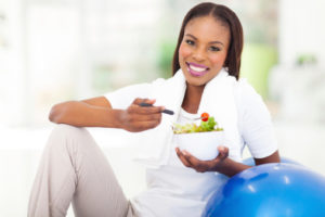 young african woman eating vegetable green salad